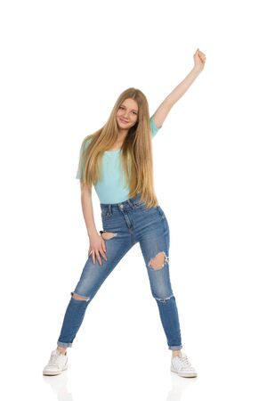 Smiling teen girl in jeans, sneakers and turquoise shirt is standing relaxed and holding arm raised. Full length studio shot isolated on white. 写真素材