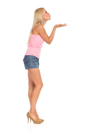 Beautiful woman in pink tank top, jeans shorts, and high is standing with hand raised and sending a kiss. Side view. Full length studio shot isolated on white.