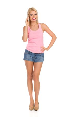Beautiful blond woman in jeans shorts, pink tank top, and high heels is standing and talking on the phone. Front view. Full length studio shot isolated on white.