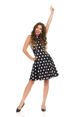 Happy beautiful young woman in black cocktail dress in polka dots and high heels is dancing, pointing up, looking away and shouting. Full length studio shot isolated on white.