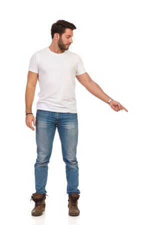 Serious handsome young man in jeans and white t-shirt is standing, pointing down and looking away. Front view. Full length studio shot isolated on white.