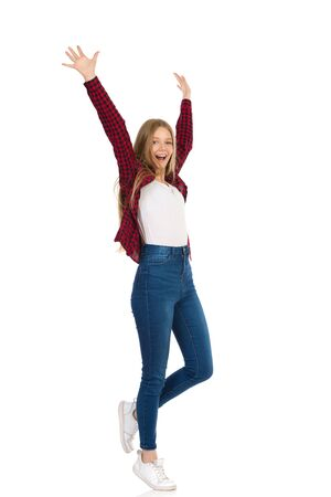 Teenager girl in jeans, sneakers and unbuttoned lumberjack shirt is standing, holding arms raised, looking at camera and shouting. Full length studio shot isolated on white.