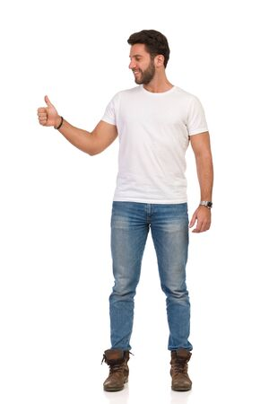 Smiling handsome man in jeans and white t-shirt is standing, showing thumb up and looking away. Front view. Full length studio shot isolated on white. Stockfoto