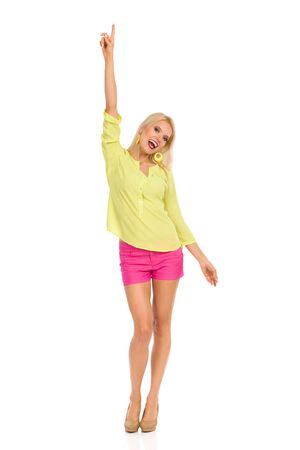 Beautiful blond woman in pink shorts, yellow shirt and high heels is standing with arm raised, pointing up and shouting. Full length studio shot isolated on white.