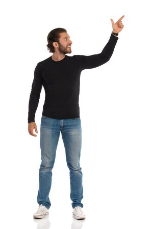 Handsome young man in jeans, sneakers and black blouse is standing, looking away and pointing up. Full length studio shot isolated on white.