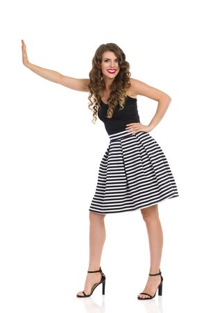 Beautiful smiling woman in striped, skirt, high heels and black top is standing, pushing or supporting something. Full length studio shot isolated on white.