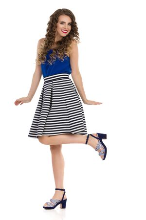 Happy young woman in striped skirt, high heels and blue top is standing on one leg, looking at camera and smiling. Full length studio shot isolated on white. Stok Fotoğraf