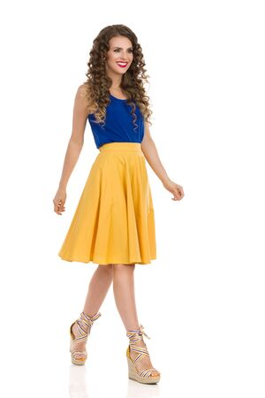 Smiling young woman in yellow skirt, blue top and wedges is walking and looking away. Full length studio shot isolated on white. Stok Fotoğraf