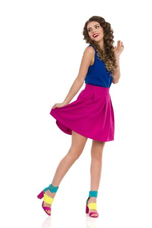 Carefree young woman in colorful high heels, pink mini skirt and blue top is standing and looking away over the shoulder. Full length studio shot isolated on white.