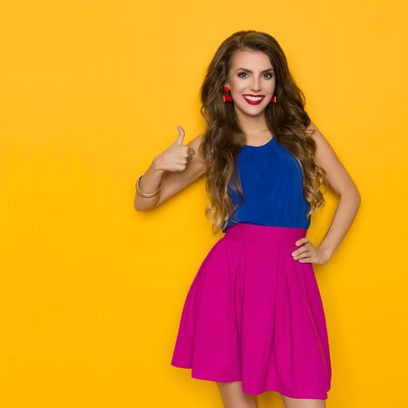 Cute young woman in vibrant clothes is showing thumb up and smiling. Three quarter length studio shot on yellow background.