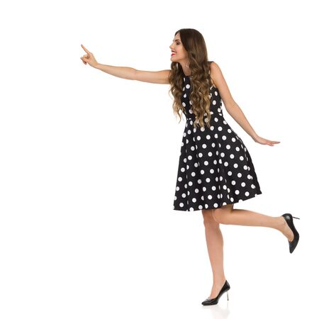 Beautiful elegant woman in black cocktail dress in polka dots and high heels is standing on one leg and trying to touch something. Full length studio shot isolated on white.