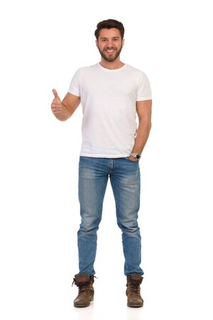 Happy handsome man in jeans and white t-shirt is standing and showing thumb up. Full length studio shot isolated on white.