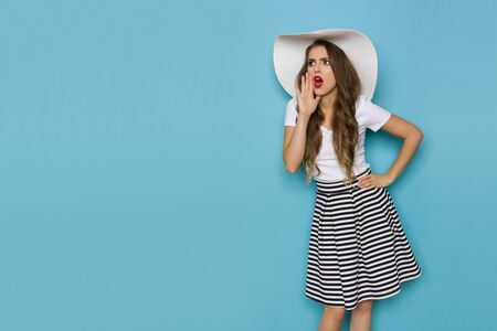 Beautiful young woman in striped mini skirt, white top and big sun hat is holding hand on chin, looking away at copy space and shouting. Three quarter length studio shot on blue background.