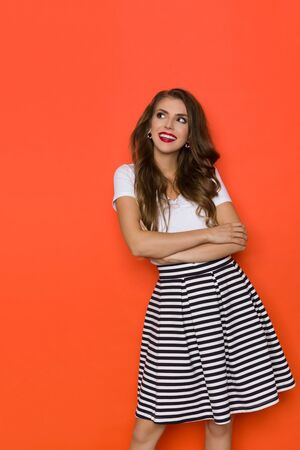 Cute young woman in striped mini skirt and white top is holding arms crossed, looking away and smiling. Three quarter length studio shot on orange background.