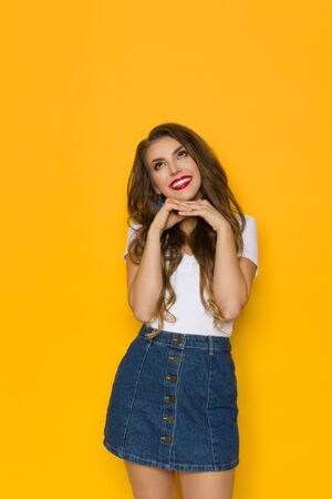Lovely young woman in jeans mini skirt and white top is holding hand on chin, looking up and dreaming. Three quarter length studio shot on yellow background.