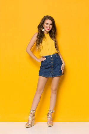 Beautiful fashion model in jeans mini skirt, wegdes and yellow top is posing with hand on hip. Full length studio shot against yellow background.
