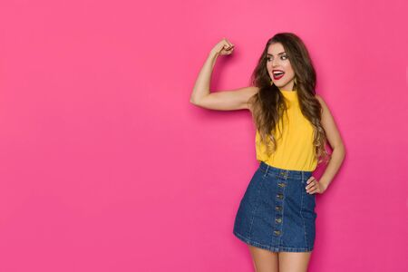 Happy beautiful woman in jeans mini skirt and yellow top is flexing muscles, looking away and talking. Three quarter length studio shot on pink background.