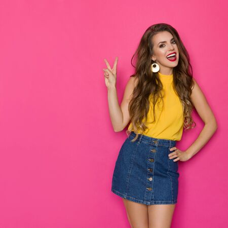 Happy young woman in jeans mini skirt and yellow top is showing peace hand sign and talking. Three quarter length studio shot on pink background. Stockfoto