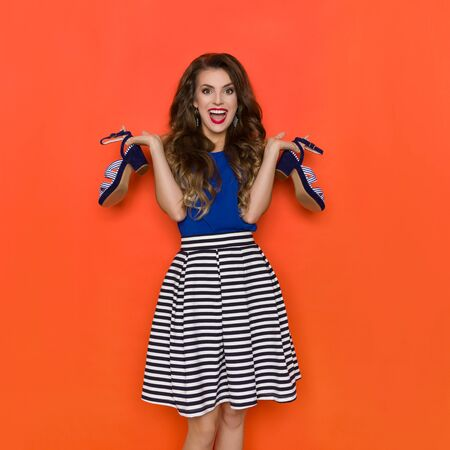 Happy and excited young woman in striped mini skirt and blue top is holding two high heel shoes and shouting. Three quarter length studio shot on orange background.