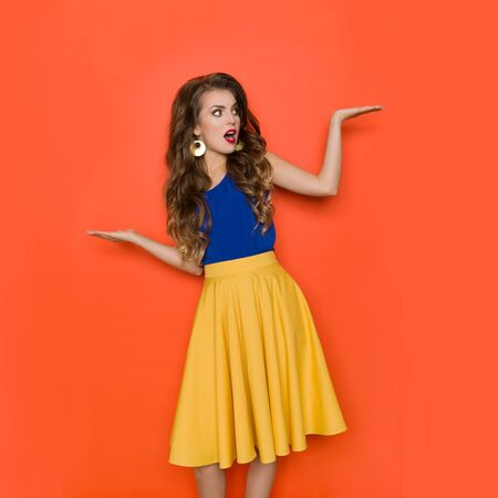 Surprised beautiful young woman is holding hands raised, compares something and looking away. Three quarter length studio shot on orange background.