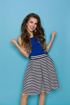 Smiling young woman in striped skirt and blue top is clenching fists. Three quarter length studio shot on blue background.