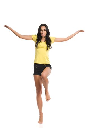 Excited young woman in yellow shirt and black shorts is standing barefoot on one leg, holding arms outstretched, looking at camera and smiling. Full length studio shot isolated on white. Banque d'images