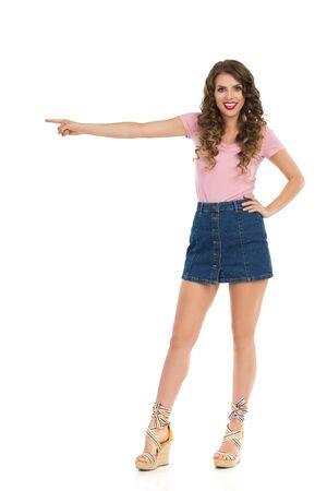 Une jeune femme souriante et confiante en mini-jupe en jean, haut rose et chaussures à plateforme se tient les jambes écartées, regardant la caméra, pointant et parlant. Tourné en studio pleine longueur isolé sur blanc.