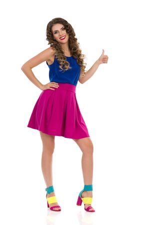 Zelfverzekerde lachende jonge vrouw in kleurrijke hoge hakken, roze minirok en blauwe top staat en toont duim. Vooraanzicht. Volledige lengte studio opname geïsoleerd op wit.