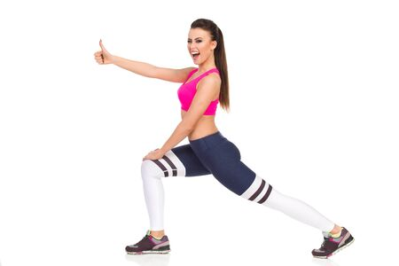 Fitness woman showing thumb up, doing lunges exercises, shouting and looking at camera. Full length studio shot isolated on white.