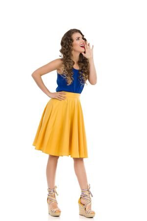 Beautiful young woman in yellow skirt, blue top and wedge shoes is holding hand on chin, looking away and talking. Full length studio shot isolated on white. Фото со стока