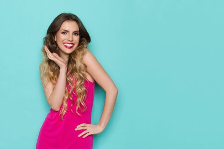 Cute young woman in pink shirt is holding hand on chin, looking at camera and smiling. Waist up studio shot on turquoise background.