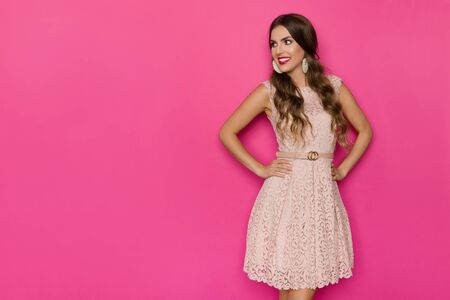 Beautiful young woman in pastel pink lace mini dress is posing with hands on hip, looking at the side and smiling. Three quarter length studio shot on pink background.