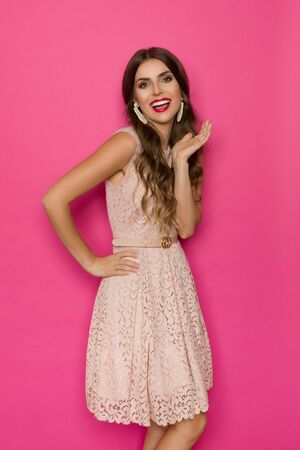 Beautiful happy young woman in beige lace mini dress is posing with hand raised and talking. Three quarter length studio shot against pink background.