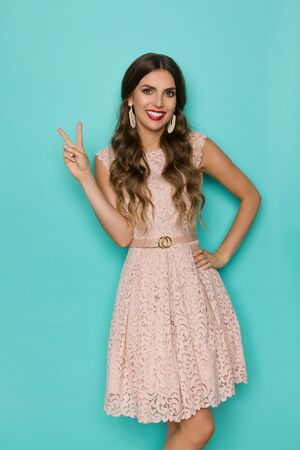 Cute young woman in beige lace mini dress is showing peace hand sign, smiling and looking at camera. Three quarter length studio shot on turquoise background.