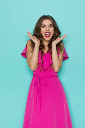 Happy and xxcited beautiful young woman in elegant pink dress is holding hands raised, and shouting. Three quarter length studio shot on turquoise background. Stock fotó