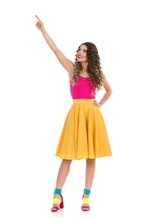 Beautiful young woman in colorful high heels, vibrant yellow skirt and pink top standing, looking up and directing. Front view. Full length studio shot isolated on white.