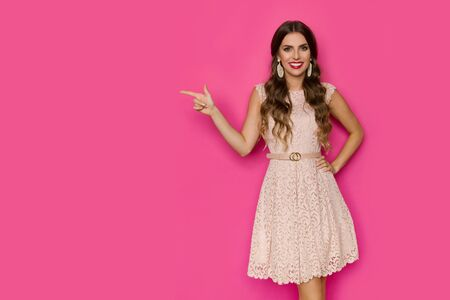 Elegant young woman in beige lace mini dress is pointing at the side and looking at camera. Three quarter length studio shot on pink background. Stock fotó