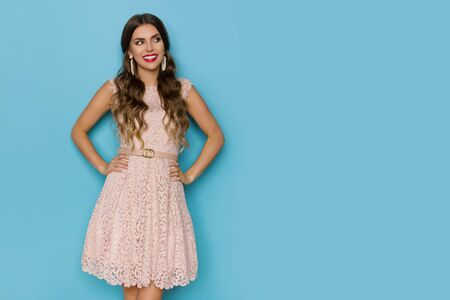 Cheerful young woman in elegant beige lace mini dress is holding hands on hip and looking away. Three quarter length studio shot on blue background.