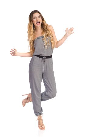 Happy young woman in dotted jumpsuit and high heels is standing on one leg, dancing and shouting. Full length studio shot on isolated on white.