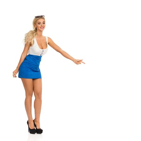 Excited blond woman in mini dress with neckline and high heels is standing, pointing down and smiling. Full length studio shot isolated on white. Stockfoto
