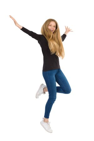 Teenager girl in jeans, sneakers and black blouse is jumping with arms outstretched and looking at camera. Full length studio shot isolated on white. Stock Photo