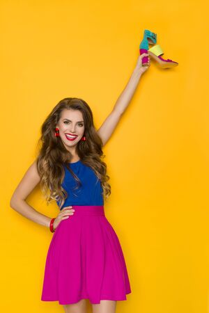 Beautiful young woman in pink mini skirt and blue top is holding colorful high heel shoe and smiling. Three quarter length studio shot on yellow background.