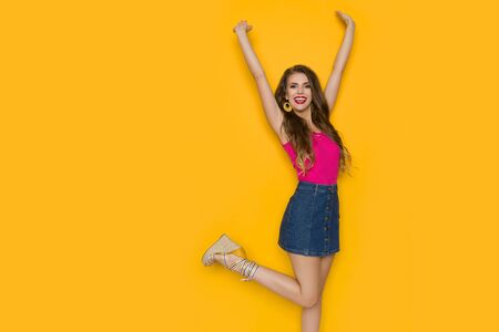 Excited young woman in jeans mini skirt and pink top is standing on one leg, holding arms raised and laughing. Studio shot on yellow background.