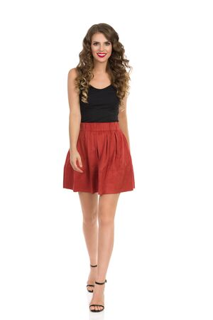 Smiling young woman in brown suede mini skirt, black top and high heels is walking towards camera. Front view. Full length studio shot isolated on white. Standard-Bild