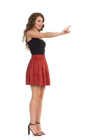 Beautiful young woman in brown suede mini skirt, black top and high heels is looking away and pushing something with index finger. Side view. Full length studio shot isolated on white.