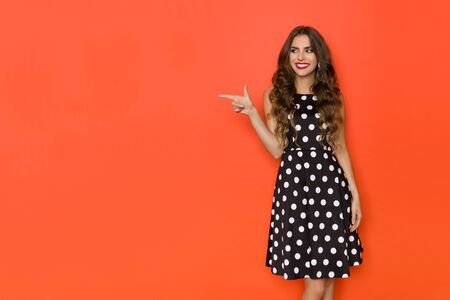 Cute woman in elegant black cocktail dress in polka dots pattern is looking away, smiling and pointing at the side. Three quarter length studio shot on orange background.