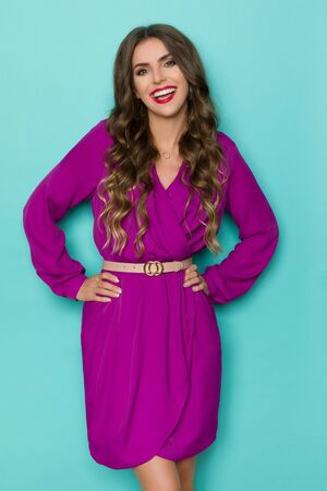 Laughing beautiful young woman in elegant purple dress is posing with hands on hip. Three quarter length studio shot on turquoise background.