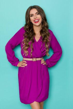Roześmiana piękna młoda kobieta w eleganckiej fioletowej sukience pozuje z rękami na biodrze. Trzy czwarte długości studio strzał na turkusowym tle.