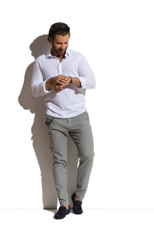 Handsome man in white shirt, gray trousers and moccasins leans against sunny wall and checks the time on a watch. Front view. Full length studio shot. Stock Photo