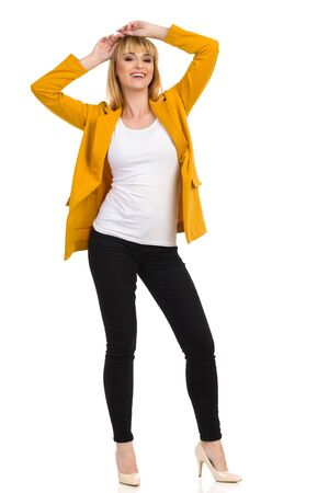 Beautiful smiling woman in unbuttoned yellow jacket is standing with arms raised and holding hands on her head. Full length studio shot isolated on white.